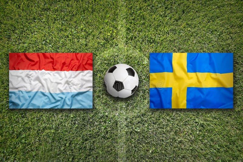 De vlaggen van Luxemburg en van Zweden op voetbalgebied stock afbeelding