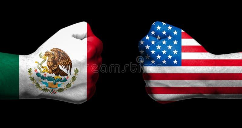 De vlaggen van Mexico en Verenigde Staten schilderden op twee dichtgeklemde vuisten die elkaar op zwarte achtergrond/Mexico onder stock fotografie