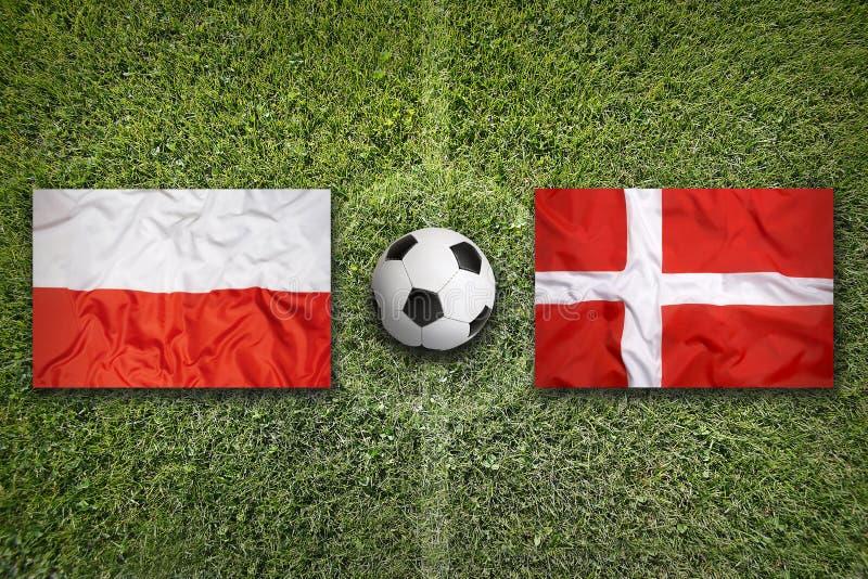 De vlaggen van Polen en van Denemarken op voetbalgebied royalty-vrije stock fotografie