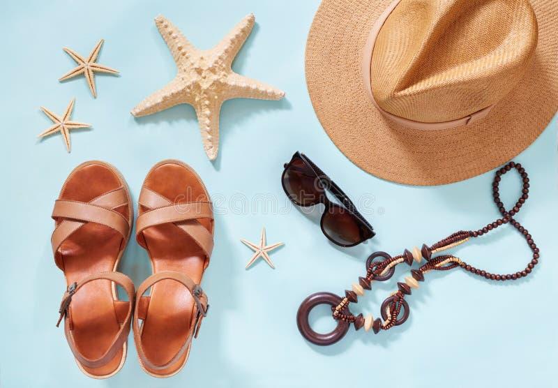 De vlakke achtergrond van de de zomervakantie, legt de toebehoren van strandvrouwen ` s: de strohoed, armbanden, leersandals, zon royalty-vrije stock afbeeldingen