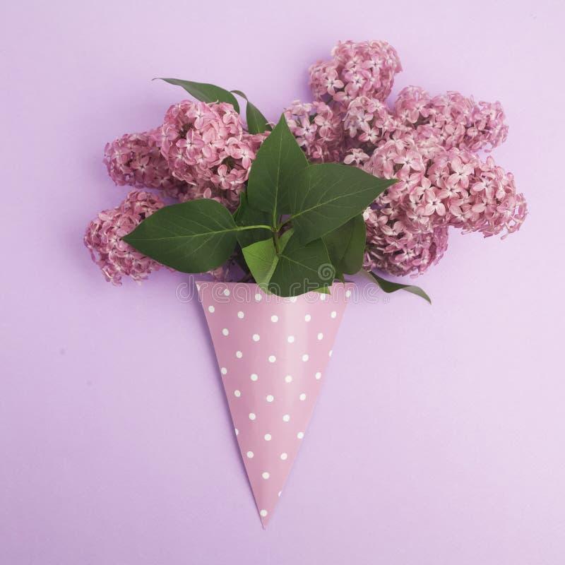 De vlakke bos van lilac bloemen in document kegel op purpere achtergrond van hierboven, legt royalty-vrije stock afbeeldingen