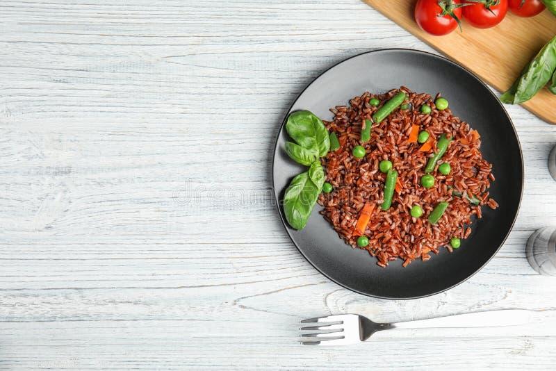 De vlakke plaat van ongepelde rijst met groenten op witte houten lijst, legt royalty-vrije stock afbeelding