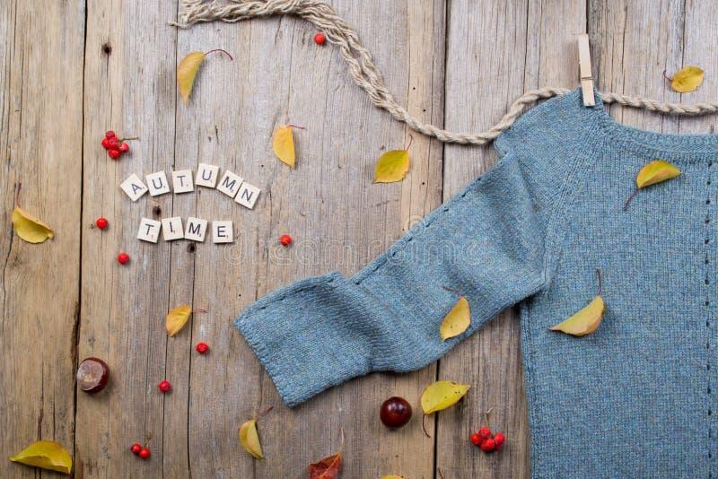 De vlakte van de de herfstdaling legt, verwarmt gebreide sweater, valt Bladeren, kastanjes, lijsterbessenbes en pompoen met de ti stock afbeelding
