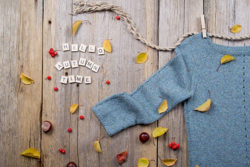 De vlakte van de de herfstdaling legt, verwarmt gebreide sweater, valt Bladeren, kastanjes, lijsterbessenbes en pompoen met de ti royalty-vrije stock foto