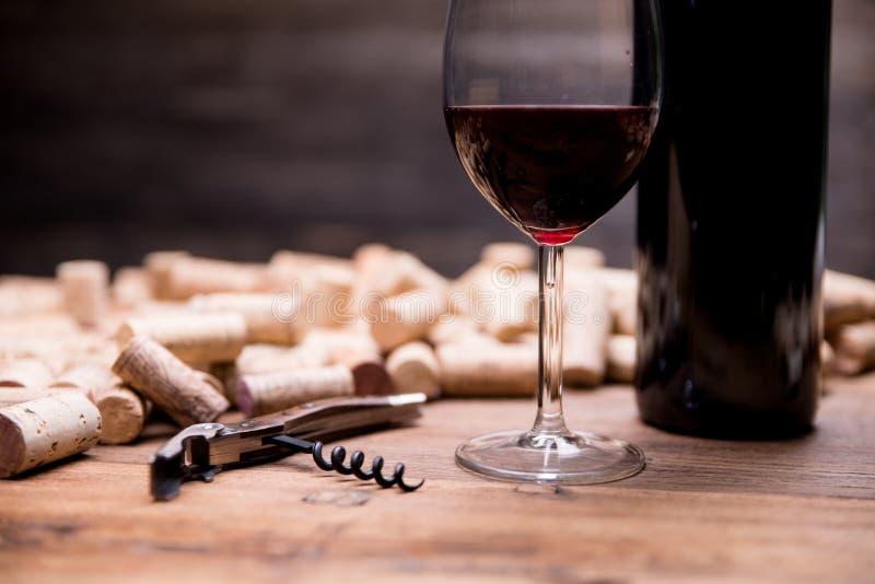 De vlakte van het wijnconcept legt stilleven met wijnfles en het glas wijn, kurkt en kurketrekker stock afbeeldingen