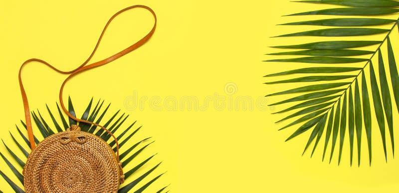 De vlakte van de de zomermanier lag Modieuze met de hand gemaakte natuurlijke ronde rotanzak en tropische palmbladen op gele acht stock afbeelding