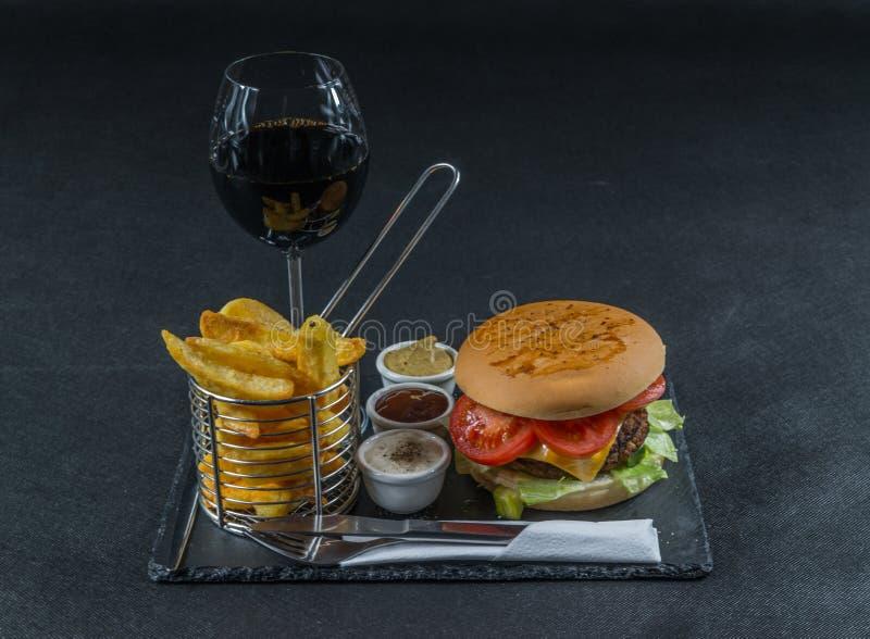 De vlam roosterde dubbele stapelcheeseburger, sla, tomaat, met t stock afbeelding