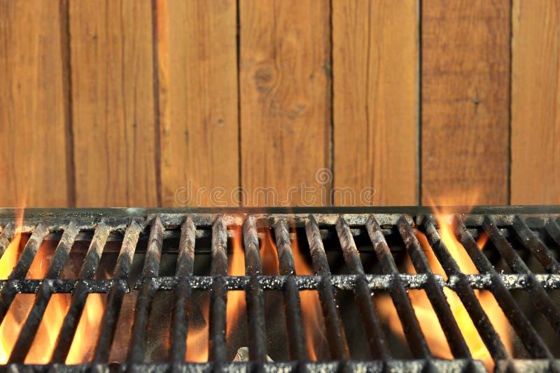 De vlammende BBQ Grill van het HoutskoolGietijzer en Houten Achtergrond stock afbeeldingen