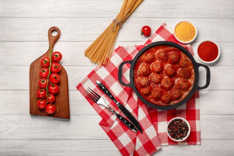 De vleesballetjes in tomatensaus met kruiden in een pan en kersentomaten op een knipsel schepen en witte houten raad in stock afbeeldingen