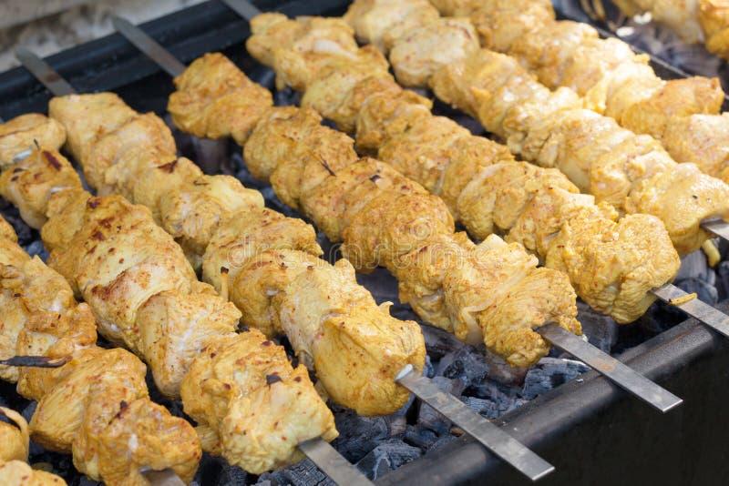 De vleespennen van Turkije die met kruiden op de grill worden gemarineerd stock fotografie