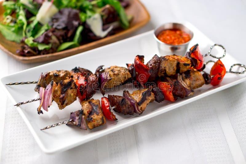 De vleespennen van varkensvleeskebabs met saus en salade stock foto
