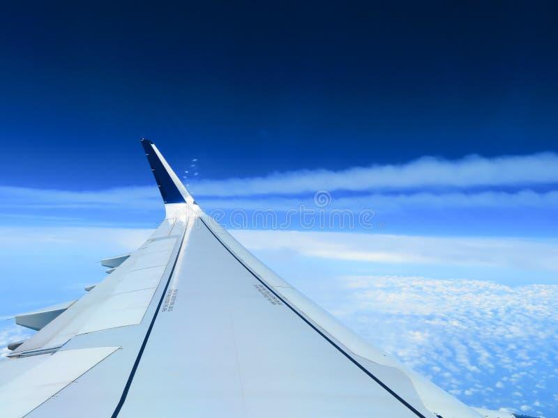 De vleugel van een vliegtuig boven de witte wolken stock fotografie