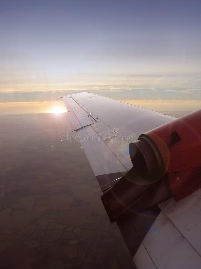 De vleugel van het vliegtuig met zongloed stock foto's