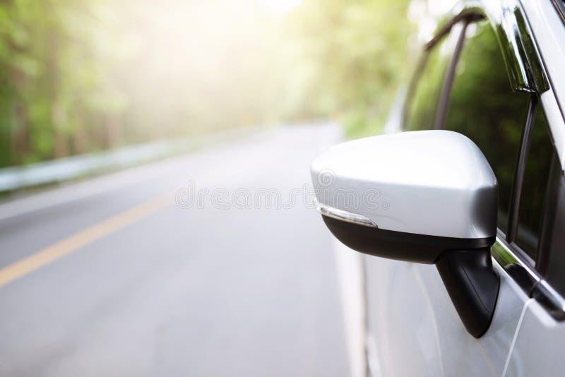 De vleugelachteruitkijkspiegel van een auto op de kant van de weg met straat die van de aard de lange weg wordt geparkeerd royalty-vrije stock foto