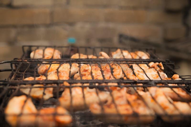 De vleugels van de kebabskip op de grill met rookclose-up Brokken van kippenbarbecue op de brand Binnenplaats, concept rust, vlee stock afbeelding