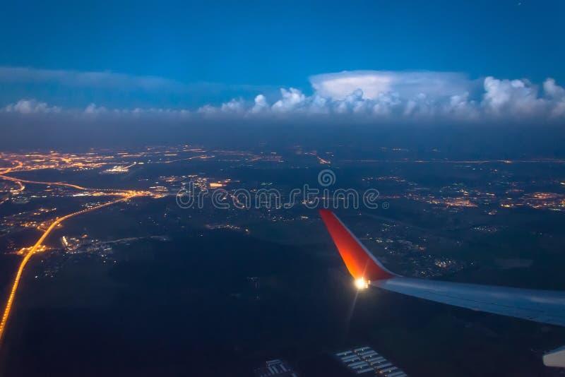 De vlieg van de vleugelmening over de stad bij nacht en onweerswolken bij de horizon royalty-vrije stock fotografie