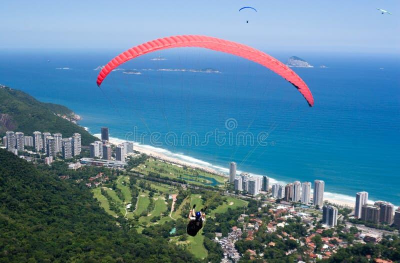 De Vliegen van het glijscherm over Rio stock foto