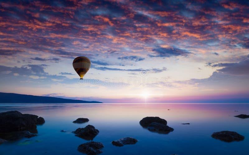 De vliegen van de hete luchtballon in gloeiende zonsonderganghemel boven kalme overzees royalty-vrije stock afbeelding