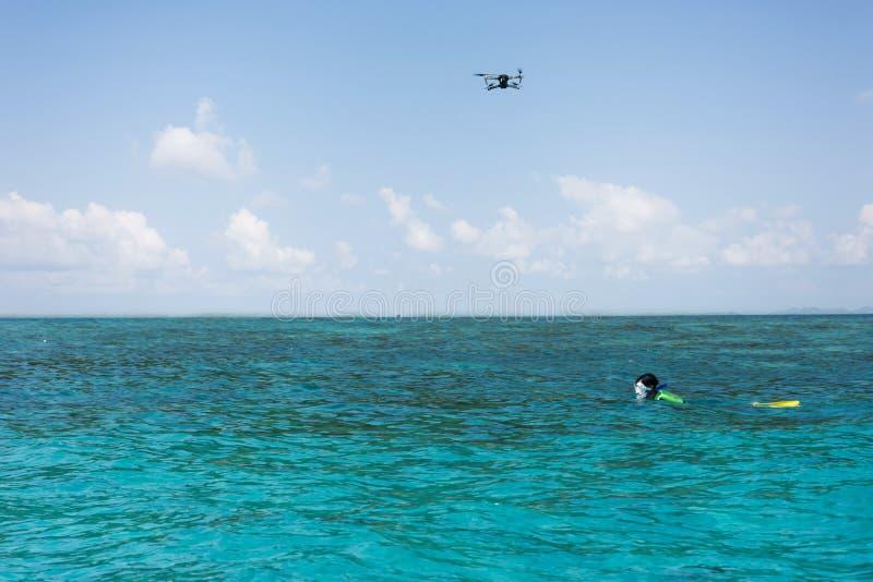 De vliegende hommel op hemel volgt duiker het snorkelen stock afbeelding