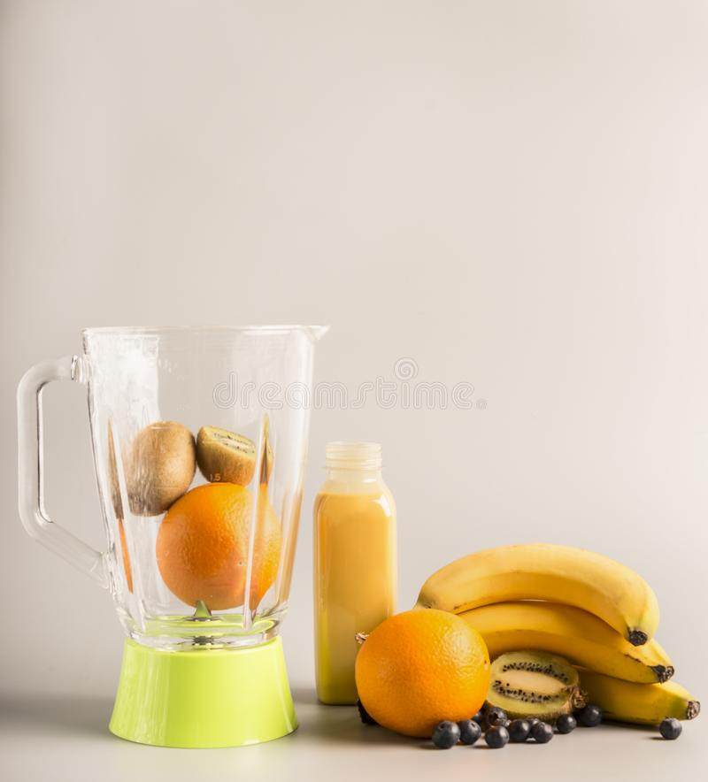 De vliegende ingrediënten voor het maken smoothies van sinaasappelen, kiwi en bananen, vegetarisch gezond voedsel, fruit voerden  stock afbeeldingen