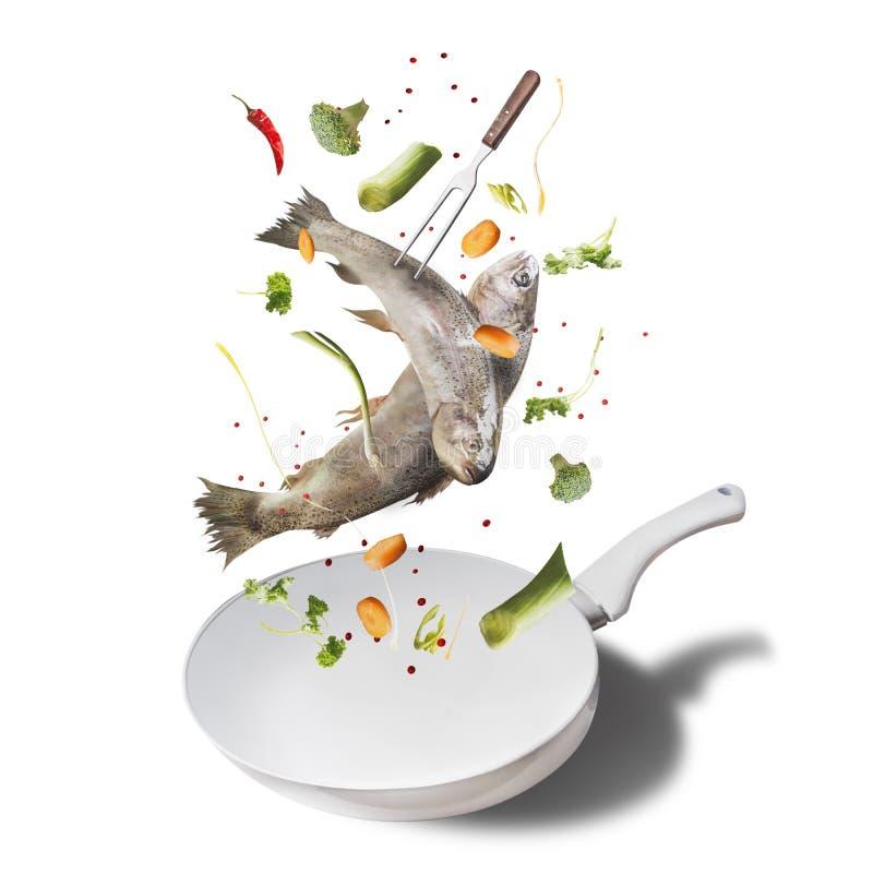 De vliegende ruwe gehele forel vist met groenten, olie en kruideningrediënten boven emailpan voor het smakelijke koken, geïsoleer stock afbeeldingen