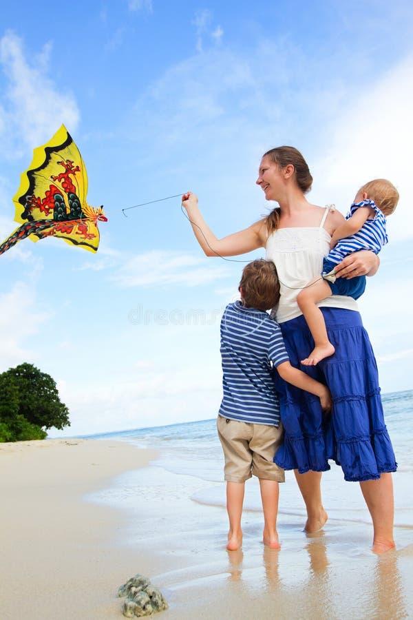 De vliegende vlieger van de familie op tropisch strand royalty-vrije stock foto