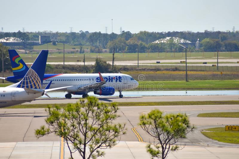 De vliegtuigen van Spirit Airlines en United Airlines-op baan die voor vertrek van Orlando International Airport MCO voorbereidin royalty-vrije stock afbeeldingen