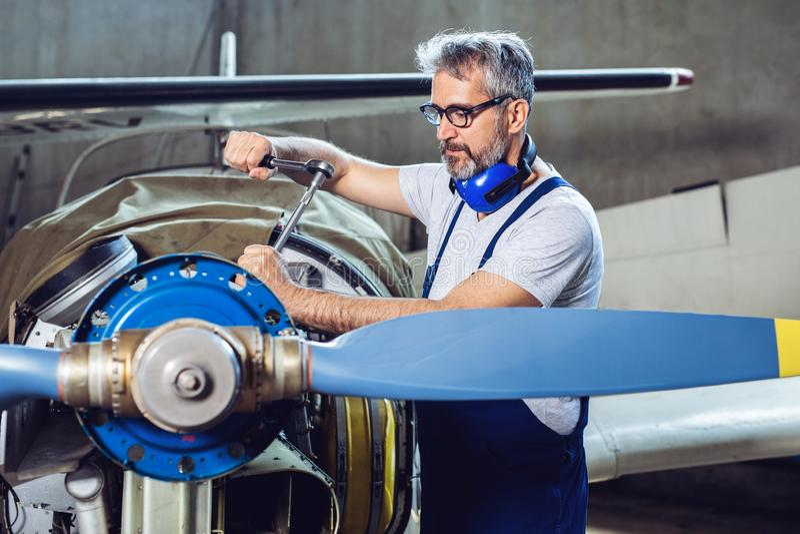 De vliegtuigenwerktuigkundige herstelt een vliegtuigenmotor royalty-vrije stock foto's