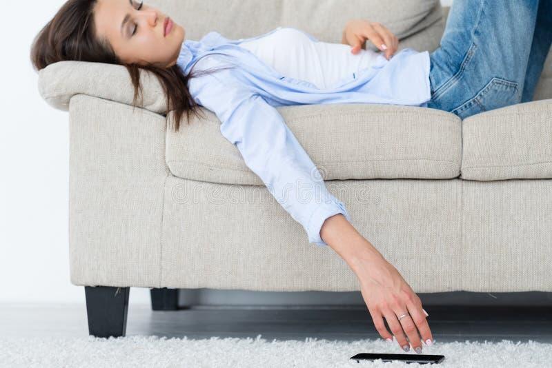 De vloerhand van de vrouwen in slaap mobiele telefoon nutteloze vrije tijd stock fotografie