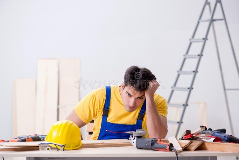 De vloerhersteller met zijn werk wordt teleurgesteld dat stock fotografie