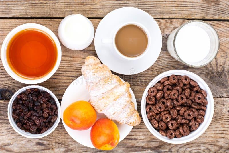 De vlokken, de koffie, de melk, het croissant en het fruit van het chocoladegraangewas voor B stock afbeeldingen