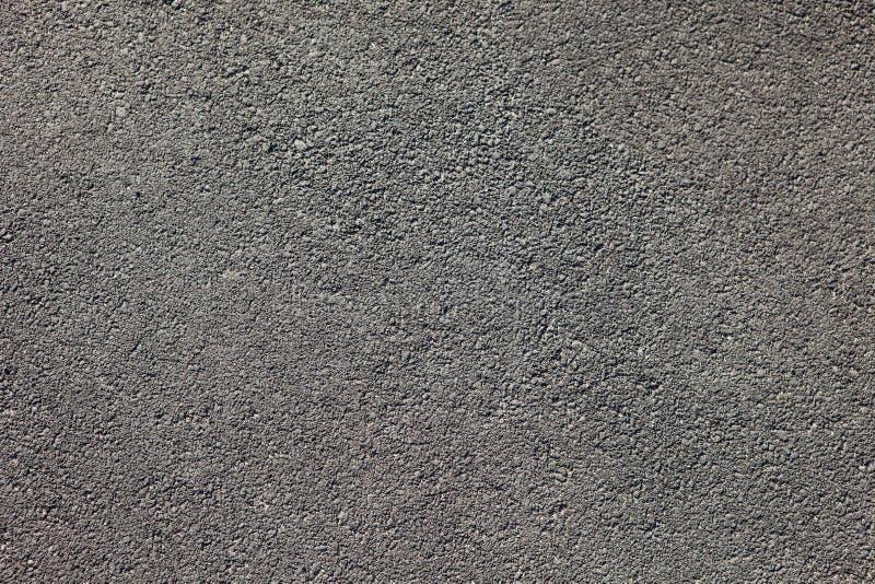 De vlotte donkere grijze textuur van de asfaltbestrating met kleine rotsen stock afbeeldingen