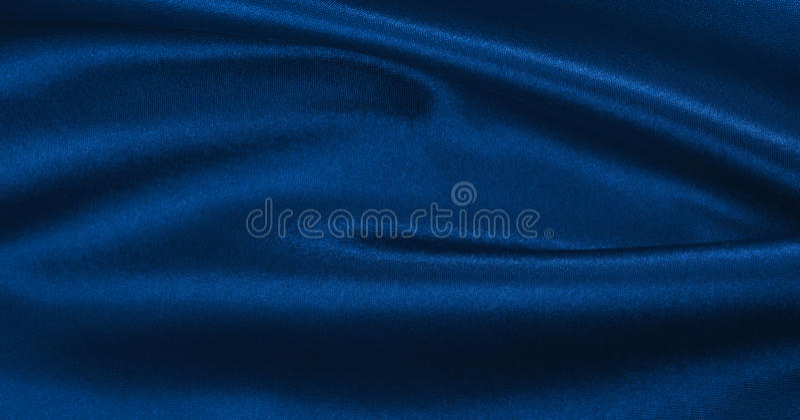 De vlotte elegante blauwe zijde of satijntextuur van de luxedoek als abstra stock afbeelding