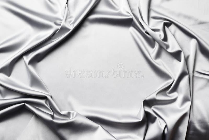 De vlotte elegante grijze zijde of satijntextuur kan als abstracte achtergrond gebruiken stock afbeelding
