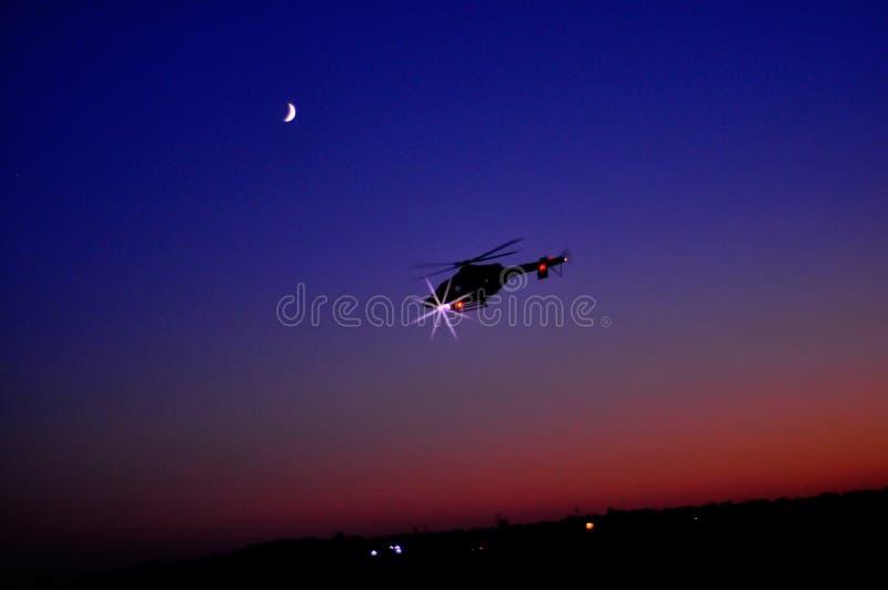 De vlucht van de helikopternacht Tegen de avondhemel royalty-vrije stock foto