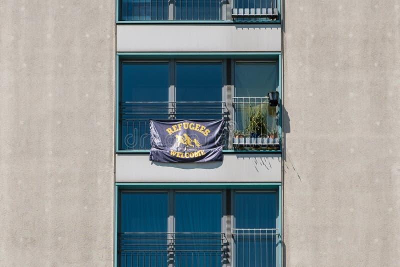 De vluchtelingen stemmen in banner met het hangen op venster van een woningbouw in Berlijn stock foto's