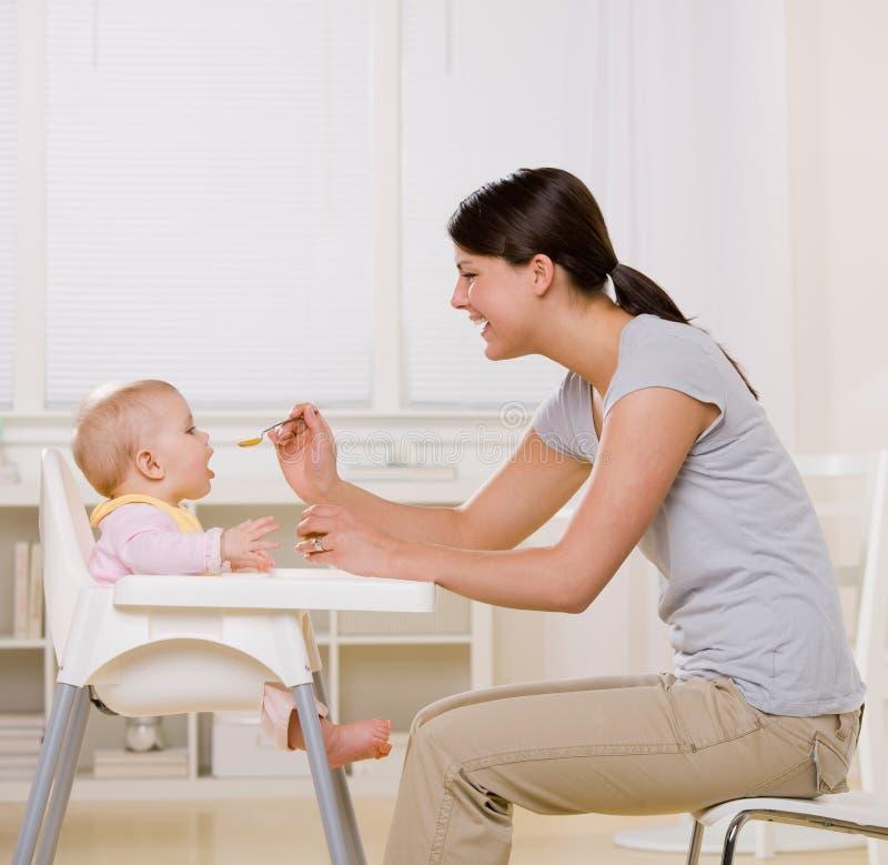 De voedende baby van de moeder in highchair in keuken stock fotografie