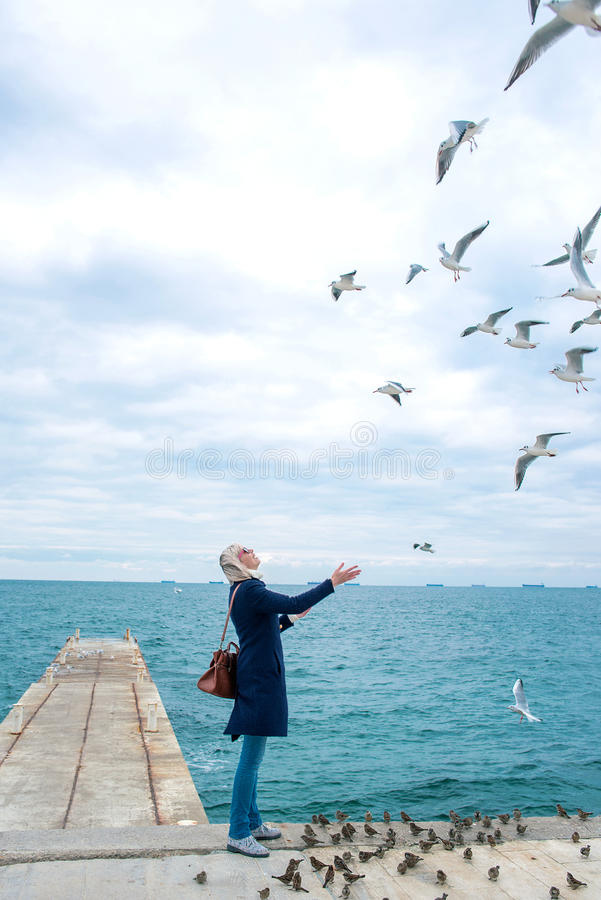 De voedende zeemeeuwen van de blondevrouw in bewolkte de herfstdag royalty-vrije stock afbeelding