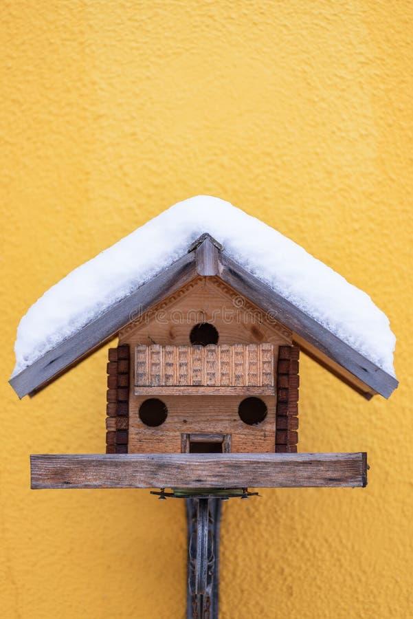 De voeder van de eigengemaakte houten vogel op de gele muur in de winter, onder sneeuw stock afbeelding