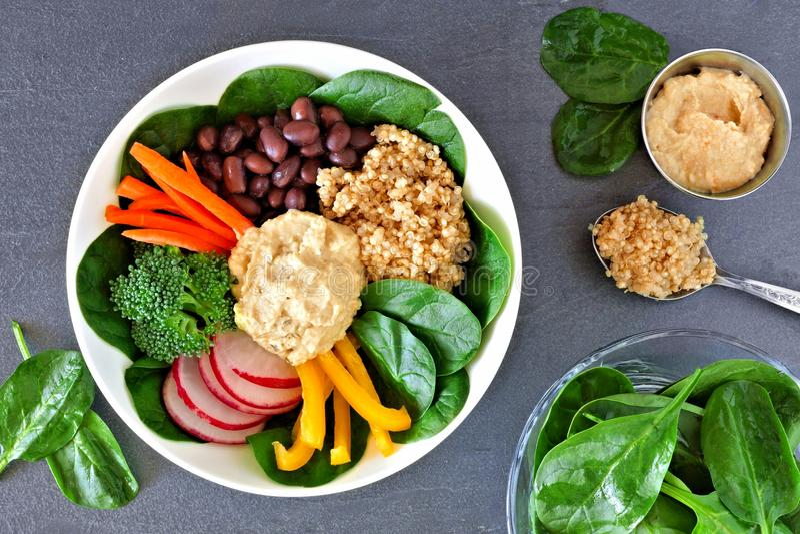 De voedingskom met quinoa, hummus, mengde groenten, luchtscène op lei royalty-vrije stock foto