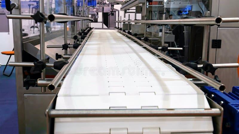 De voedselfabriek automatiseerde robotachtige transportbandlijn royalty-vrije stock afbeelding