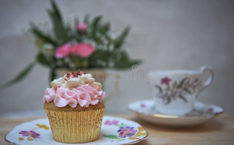 De voedselfotografie van een huis maakte cupcake met roze boterroombovenste laagje en vertroebelde bloemenachtergrond met kop en  royalty-vrije stock afbeeldingen