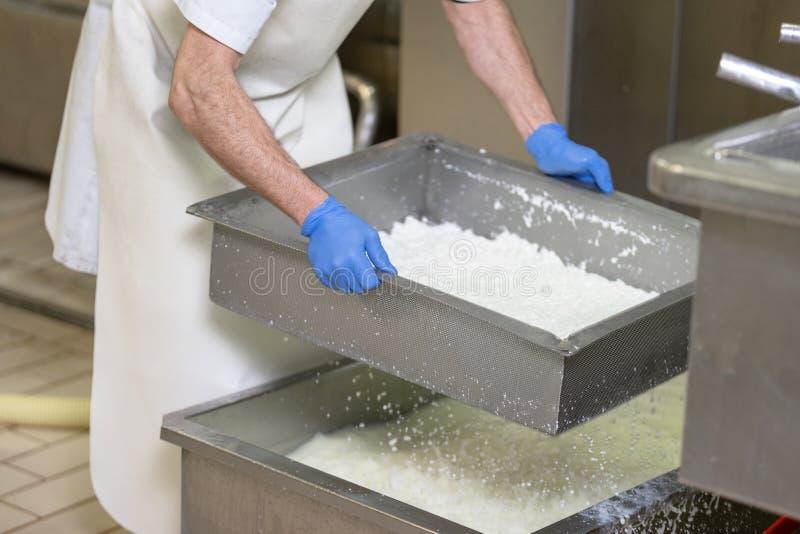 De voedselindustrie Arbeider die de voorwaarden van gisting van de kaas in een roestvrij staaltank controleren royalty-vrije stock foto