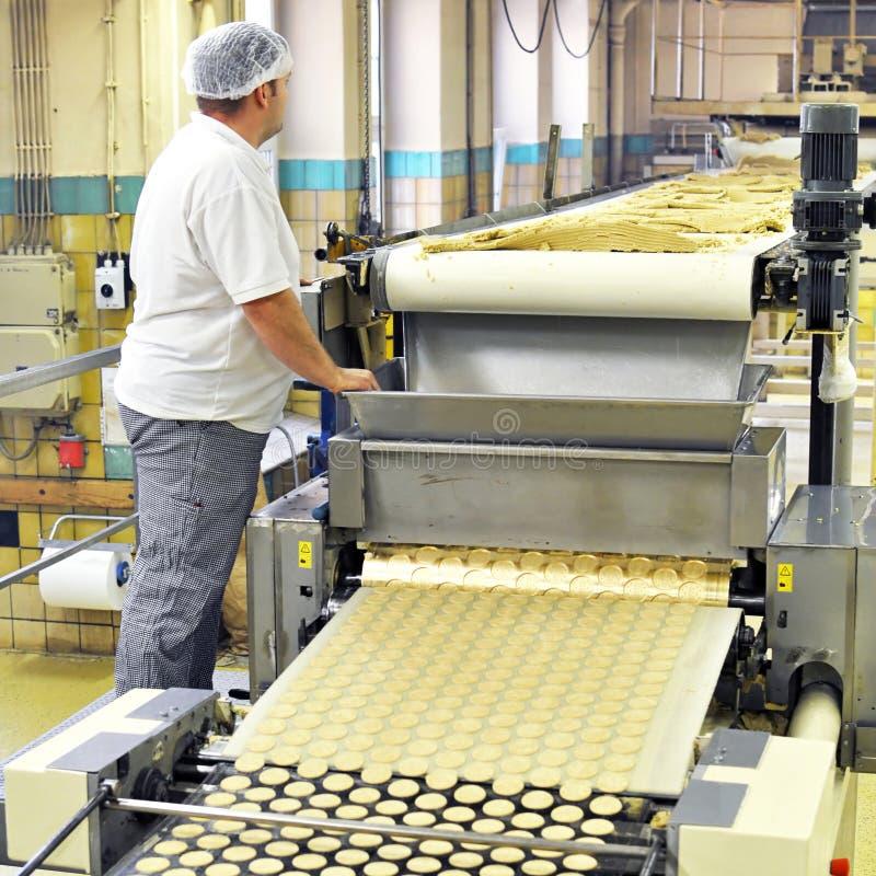De voedselindustrie - de koekjesproductie in een fabriek op een transportband is royalty-vrije stock afbeeldingen