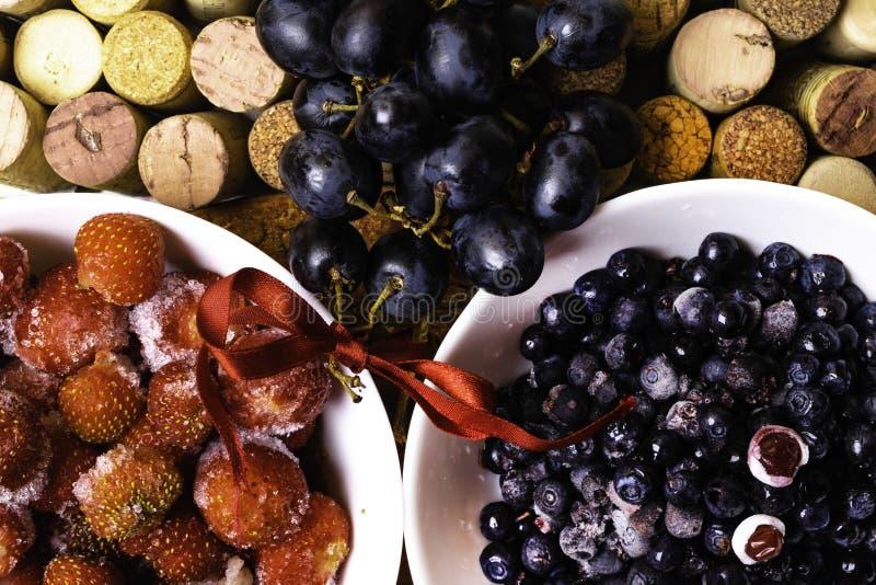 de voedselrijken met resveratrol, aardbei, bosbes, druif op wijn kurkt achtergrond royalty-vrije stock afbeelding