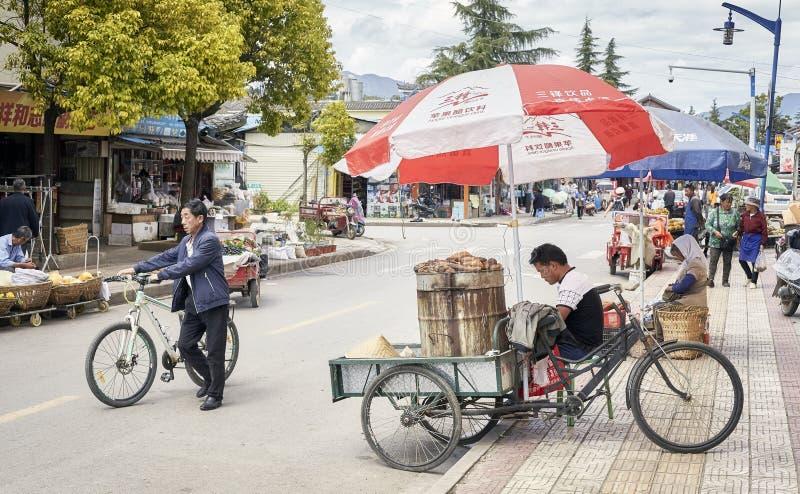 De voedselverkoper wacht op klanten met een fietsbox op een straat van Lijiang stock foto