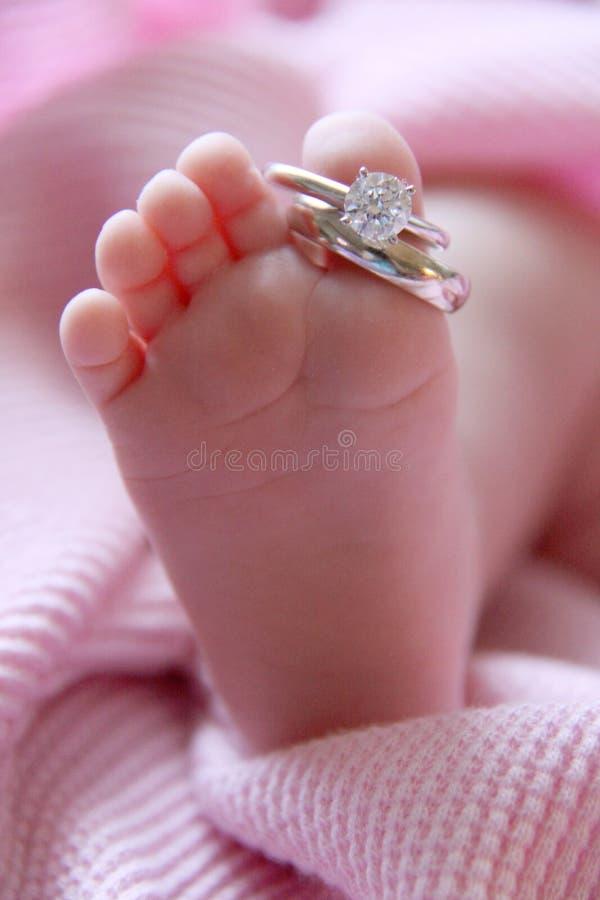 De voet en de trouwringen van de baby stock foto