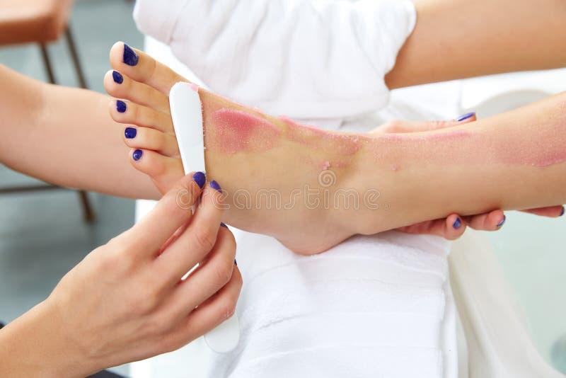 De voet schrobt het been van de pedicurevrouw in spijkersalon stock fotografie