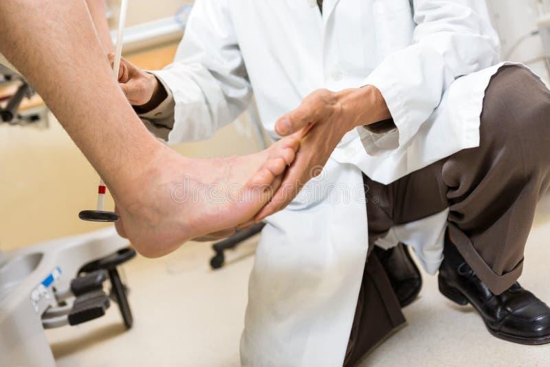 De Voet van artsenexamining patient in het Ziekenhuis stock afbeelding