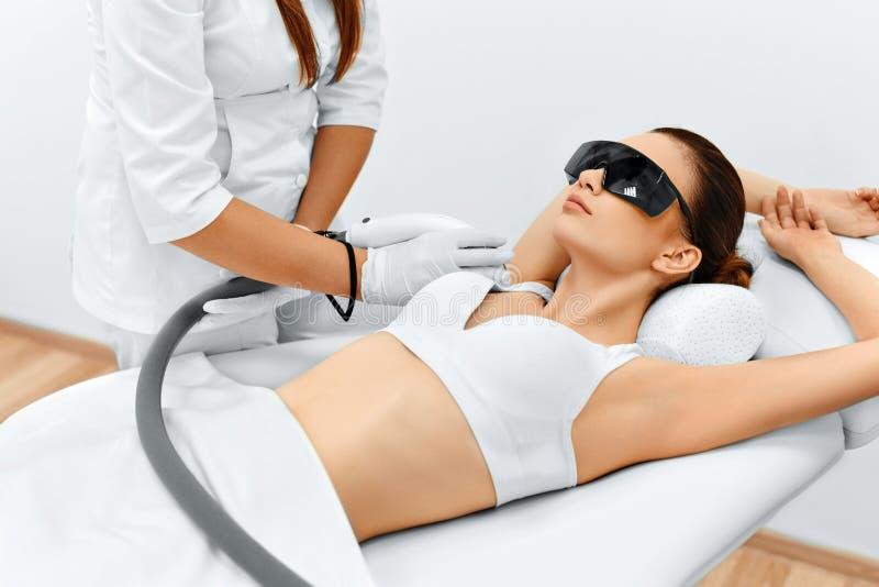 De voet van de vrouw in het water De Verwijdering van het laserhaar Epilationbehandeling Vlotte Huid stock afbeeldingen